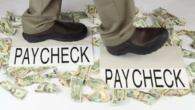 Earning and Spending Paycheck to Paycheck. Feet and legs of a man walking from paycheck to paycheck with crumpled money scattered about on a white floor stock footage