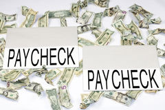 Earning to Pay. Two large paper rectangles with the word paycheck on each, surrounded by crumpled dollars of different denominations royalty free stock images