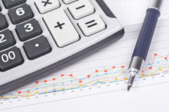 Earnings. Calculator and pen on earnings chart background. Shallow depth of field royalty free stock photos