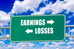 Earnings and losses sign. On the green board with clouds in background stock photos