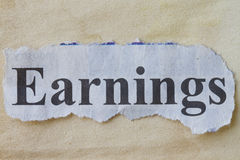 Earnings. In a newspaper cutout with vintage paper background stock photography
