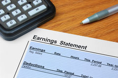 Earnings Statement. An itemized earnings statement showing earnings and deductions, on a desk with a calculator and pen Stock Images