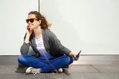 Earp de écoute de musique de belle jeune de brune de cheveux femme de hippie Photographie stock libre de droits