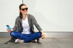 Earp de escuta da música da mulher moreno nova bonita do moderno do cabelo Imagem de Stock Royalty Free