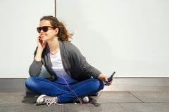 Earp de escuta da música da mulher moreno nova bonita do moderno do cabelo Fotografia de Stock Royalty Free
