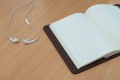 Earphone and notebook over wooden table. ready for mockupe Stock Photography