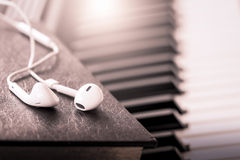 Earphone on book on piano key in vintage color tone Stock Photos