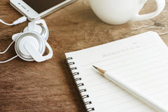 Earphone with coffee and notebook on old wooden table Stock Images