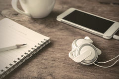 Earphone with coffee and notebook on old wooden table Stock Photo