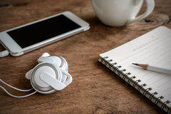 Earphone with coffee and notebook on old wooden table Stock Photos