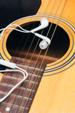 Earphone on guitar,selective focus Royalty Free Stock Image