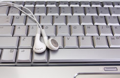 Earphone on keyboard. White earphone on silver laptop keyboard stock photo