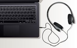 Earphone and laptop. The earphones and the laptop lying on a table Royalty Free Stock Images