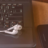 Earphone and Laptop. Royalty Free Stock Image