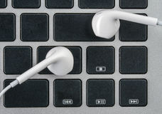 Earphone on the laptop keypad, close up, music Royalty Free Stock Images