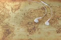 Earphone on a old world map Stock Images