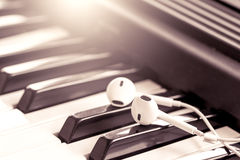 Earphone  on piano key in vintage color tone Stock Photo