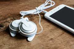 Earphone with smartphone on wooden table Stock Images