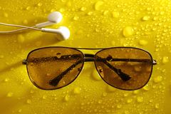 Earphone sunglasses from sun water drop on abstract yellow backg. Round. melodies of autumn. the concept of the changing seasons royalty free stock photo