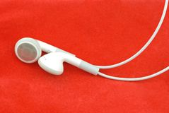 Earphones. White Earphones over red background Royalty Free Stock Image