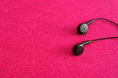 Earphones. Against a pink background Stock Image