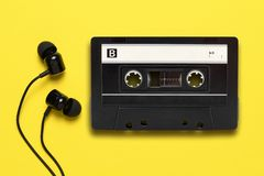Earphones and audio cassette. On yellow background stock image