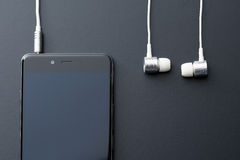 Earphones and cellphone Stock Images