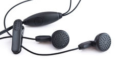 Earphones, garniture from mobile telephone. The Garniture from inexpensive mobile telephone, with special clothes-peg, for fastening to cloth, black colour Stock Photos