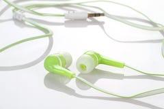 Earphones Headphones on Reflective White Background Royalty Free Stock Photos
