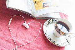 Earphones heart with book and cup of coffee on pink fabric backg Stock Images