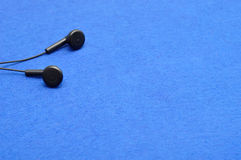 Earphones. Isolated against a blue background Royalty Free Stock Images