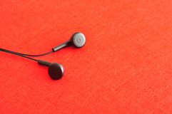 Earphones. Isolated against a red background Royalty Free Stock Photography