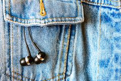 Earphones on a jeans background Royalty Free Stock Images