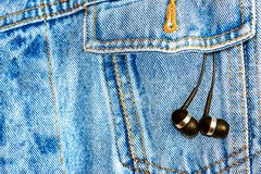 Earphones on a jeans background Stock Photos