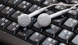 Earphones on keyboard thai and english Royalty Free Stock Photos