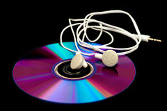 Earphones lying on a compact disc Stock Images