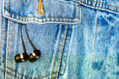 Earphones on a jeans background Stock Images