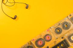 Earphones and retro cassette on yellow background. copy space. Headphones and retro cassette on yellow background royalty free stock photography