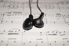 Earphones on sheet music Royalty Free Stock Photo