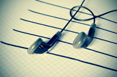 Earphones on a staff simulating musical notes Stock Images