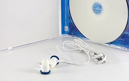 Earphones and unlabeled white blank DVD Stock Photography