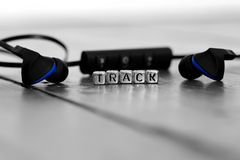 Earphones on a wooden floor with the word track Stock Photography