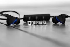 Earphones on a wooden floor with the word tunes. On beads Stock Images