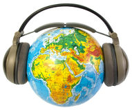 Earphones on world globe Royalty Free Stock Images
