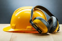 Earphones and yellow construction helmet royalty free stock images