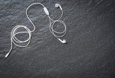 Earphons en la opini?n superior del fondo oscuro/la m?sica es mi vida y el entretenimiento escucha el concepto de la m?sica foto de archivo libre de regalías