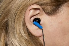 Earpiece in the human ear. Headset for communication in the human ear stock image