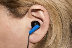 Earpiece in the human ear. Headset for communication in the human ear royalty free stock photography