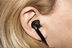 Earpiece in the human ear. Headset for communication in the human ear royalty free stock photos