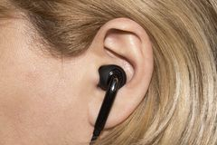 Earpiece in the human ear. Headset for communication in the human ear royalty free stock images
